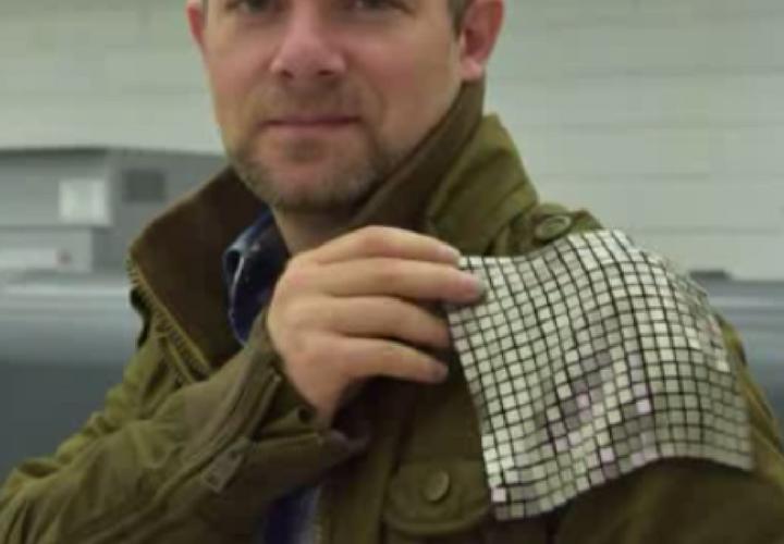 El orgulloso inventor con una pieza de tela metálica