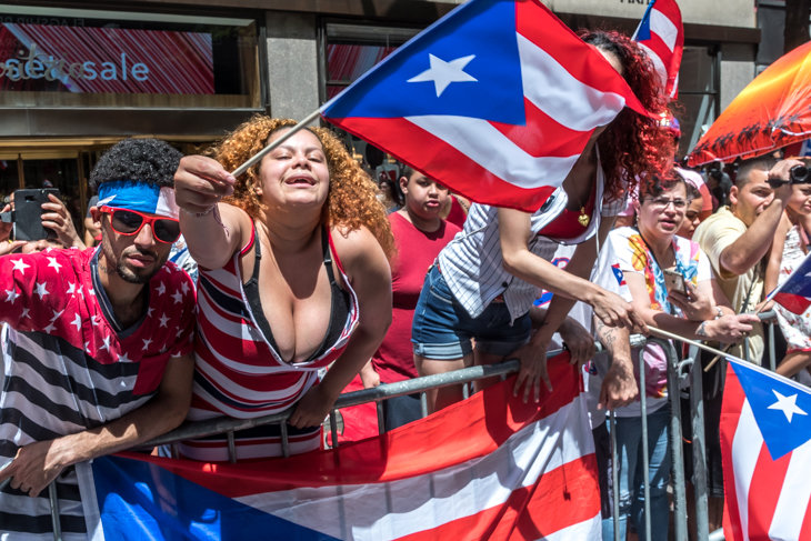 Spectators wave Puerto Rican flags as they watch the Puerto Rico Day Parade in New York's Fifth Avenue on June 11, 2017..  Photo by Enrique Shore