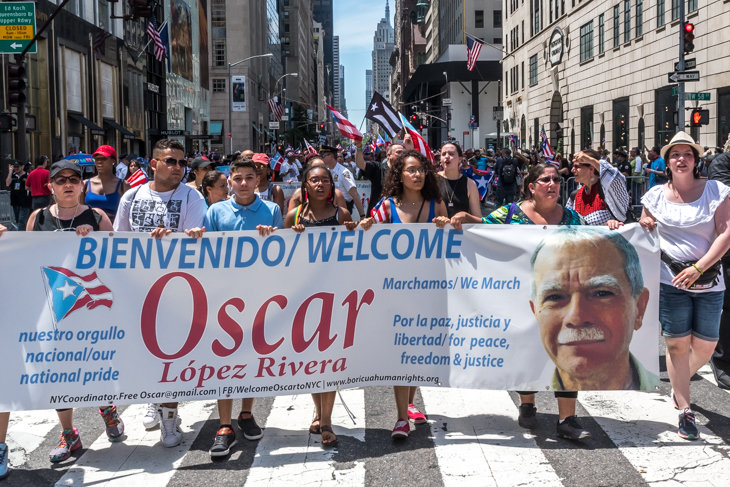 Puerto Rican independentists carry a banner welcoming  Oscar Lopez Rivera as they participate in the Puerto Rico Day Parade in New York on June 11, 2017. Lopez Rivera participated in the parade, months after being released upon serving 35 years in prison.  Photo by Enrique Shore