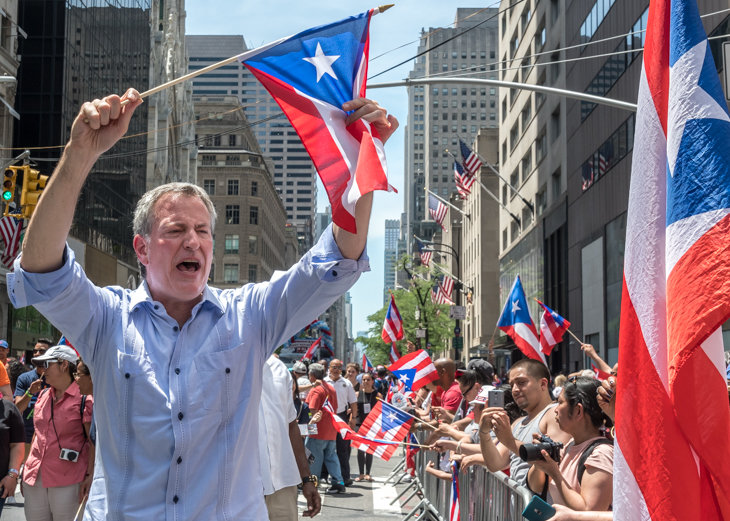 New York Mayor Bill De Blasio waves a Puerto Rican flag to spectators in Fifth Avenue during the Puerto Rico Day Parade in New York on June 11, 2017.  Photo by Enrique Shore